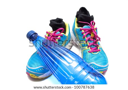Sneakers with socks and a bottle of water on white background - stock photo