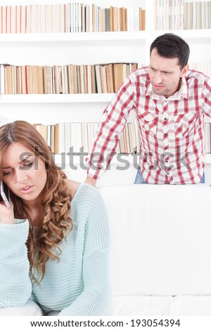 sneaky jealous possessive man spying watching woman talking on the phone, negative emotion facial expression feelings conflict concept - stock photo