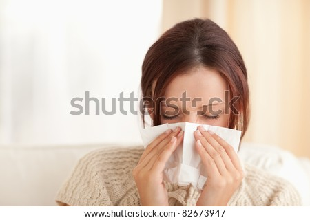 Sneezing cute woman in a living room - stock photo
