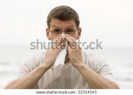 Sneezing mature man in front of the sea - stock photo