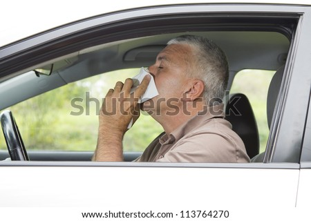 Sneezing mid aged man in the car having cold - stock photo