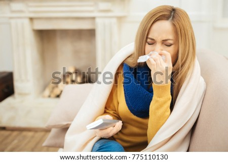 Sneezing. Sick unhappy young dark-eyed woman having runny nose and sneezing and sitting on the couch and holding remote control and a fireplace in the background