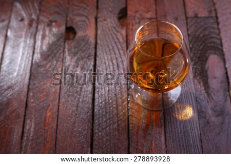 Snifter glass full of brandy standing on a wooden table