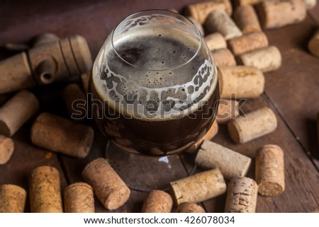 Snifter glass with dark ale beer in a cellar with wine corks