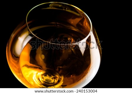 snifter of brandy in elegant glass with space for text on black background - stock photo