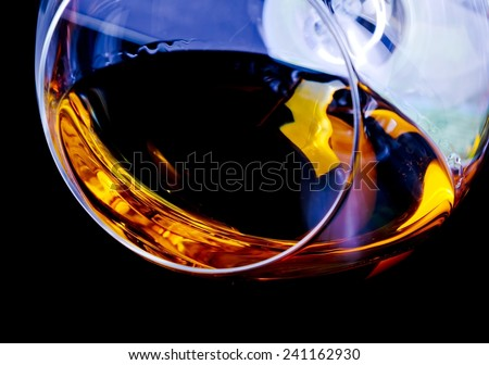 snifter of brandy in elegant glass with space for text on light tint blue disco background - stock photo