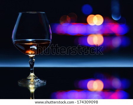 snifter with brandy on a dark background. - stock photo
