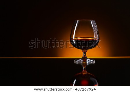 Snifter with brandy on a reflective background