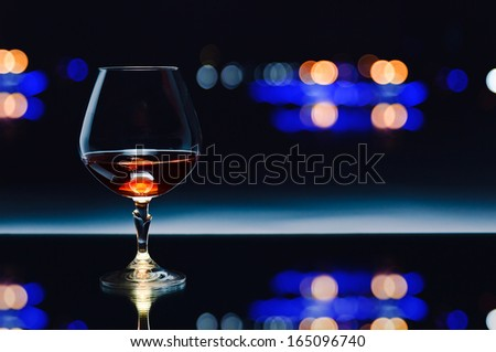 snifter with brandy on  dark background - stock photo