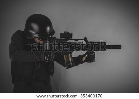 sniper, airsoft player with gun, helmet and bulletproof vest on gray background - stock photo