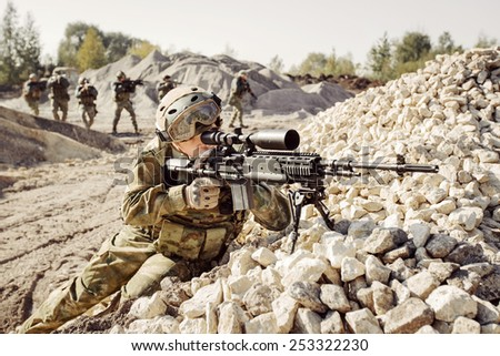 Sniper covers offensive squad of rangers - stock photo