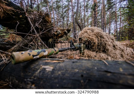 Sniper in camouflage suit is hiding and aiming behind a tree/Camouflaged sniper lying in forest and aiming through his scope - stock photo