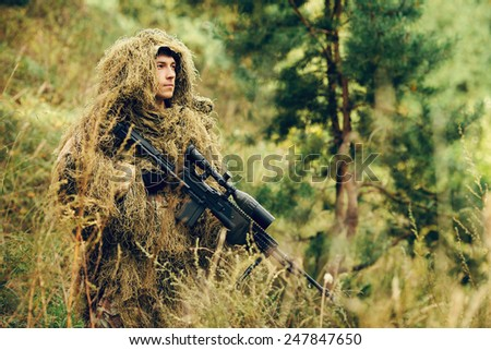 sniper in camouflage suit standing with arms and looking at the target - stock photo