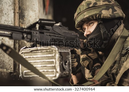 Sniper in military uniform aiming at the target - stock photo
