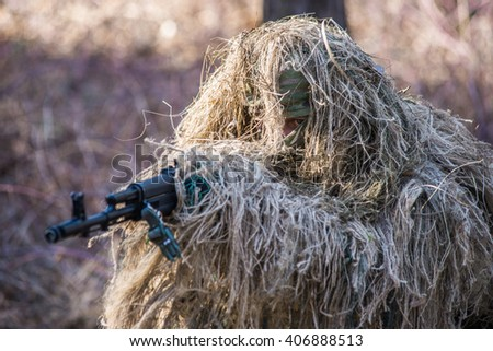 Sniper in special camouflage ghillie suit with gun.Selective focus/Ukrainian sniper wearing ghillie suit