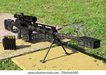 Sniper rifle .50 BMG caliber with muzzle brake. Long rifle on bipod and ammunition near is ready for shooting. - stock photo