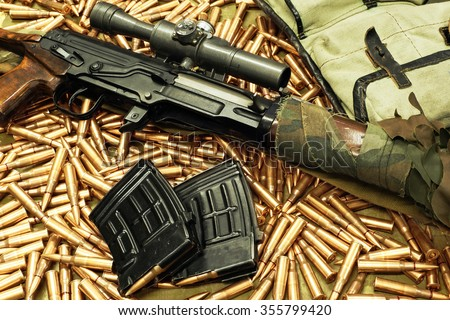 sniper rifle with weapons holders on the loose cartridges - stock photo