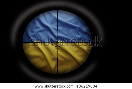 Sniper scope aimed at the Ukrainian flag - stock photo