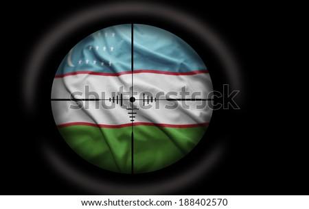 Sniper scope aimed at the Uzbek flag - stock photo