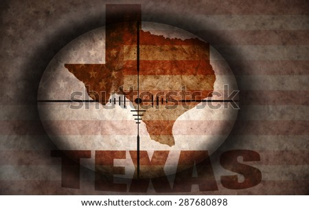 sniper scope aimed at the vintage american flag and texas state map - stock photo