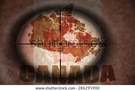 sniper scope aimed at the vintage canadian flag and map - stock photo