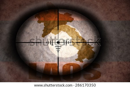 sniper scope aimed at the vintage laos flag and map - stock photo