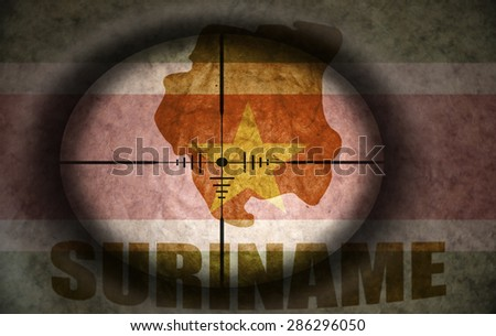 sniper scope aimed at the vintage surinamese flag and map - stock photo
