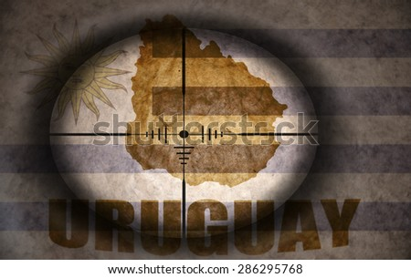 sniper scope aimed at the vintage uruguayan flag and map - stock photo