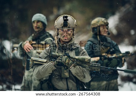 sniper stands with arms and looks forward - stock photo