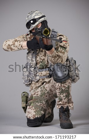 Sniper with rifle aiming over grey background