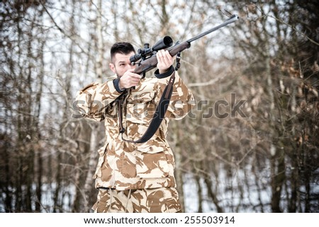 Sniper with weapon ready for combat or hunting in the forest on a winter day - stock photo