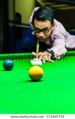 Snooker player placing the cue ball for a shot (Focus on ball,blur on player face and motion blur)