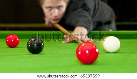 Snooker player placing the cue ball for a shot on black, whilst hitting the red ball (Selective focus and motion blur) - stock photo