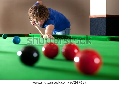 Snooker player taking a long shot across the table - stock photo
