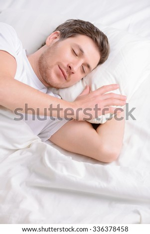 Snooze minutes. Attractive young single man doses off in his bed in the morning.  - stock photo