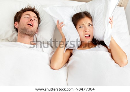 Snoring man. Couple in bed, man snoring and woman can not sleep, covering ears with pillow for snore noise. Young interracial couple, Asian woman, Caucasian man sleeping in bed at home. - stock photo