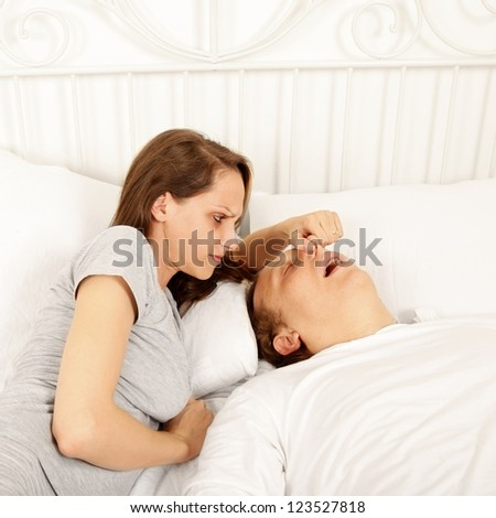 Snoring man in bed and woman covering his nose