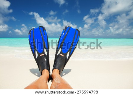 Snorkeler relaxing on the beach. Tanned legs in blue fins on the white sand, blue cloudy sky and crystal sea background. Happy island lifestyle. Vacation at Paradise. Travel to tropical beach