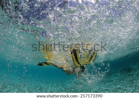 Snorkeler swimming in blue lagoon
