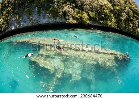 Snorkelers swim above a shipwreck in Palau's inner lagoon. Palau harbors dozens of shipwrecks, most of them sunk during World War II. - stock photo