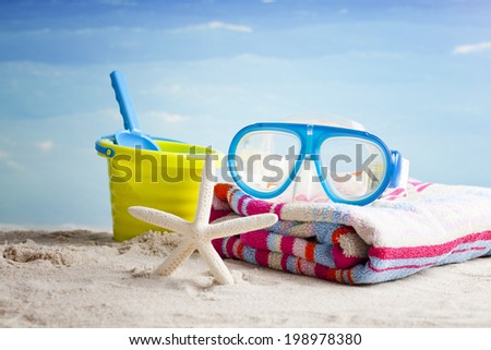 snorkeling glasses,bucket and shovel on the beach with a starfish  - stock photo