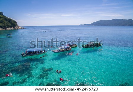 snorkeling group in clear water at perhentian island, terengganu malaysia
