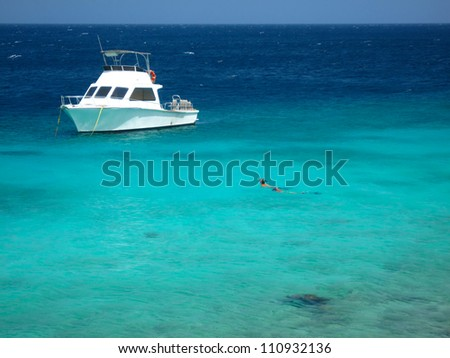 Snorkeling in Caribbean Sea with dive boat, Curacao, Netherlands Antilles,