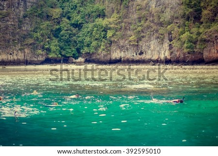 Snorkeling in one of amazing lagoons of Phi-Phi islands, Krabi, Thailand. Image with selective focus and toning - stock photo