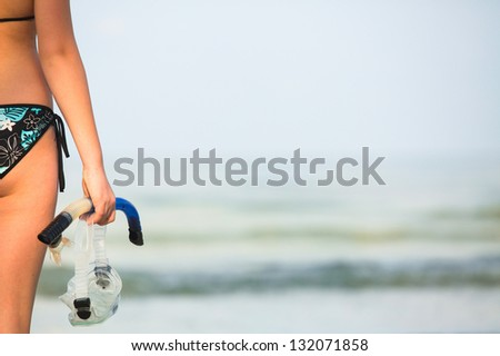 Snorkeling or diving, young woman with a snorkel and mask standing on sand and going to swim in sea (picture with space for text) - stock photo