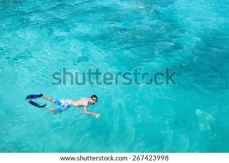 snorkeling, top view of man swimming with fins and mask, copy space