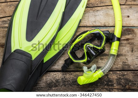 Snorkelling equipment on wood background. Flippers, mask and snorkel top view image  - stock photo