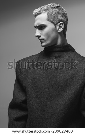 Snow Adonis fashion beauty concept. Portrait of young man in grey classic coat with stylish haircut posing over gray background. Perfect hair & skin. Vogue avant garde style. Close up. Studio shot