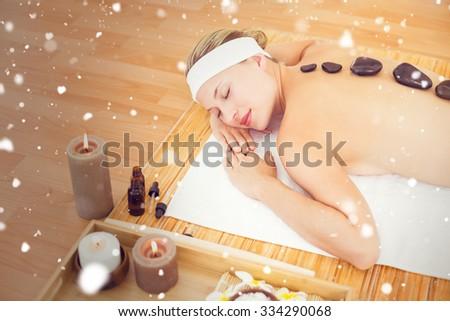 Snow against beautiful blonde enjoying a hot stone massage - stock photo