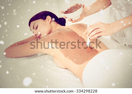 Snow against beautiful brunette enjoying a chocolate beauty treatment - stock photo